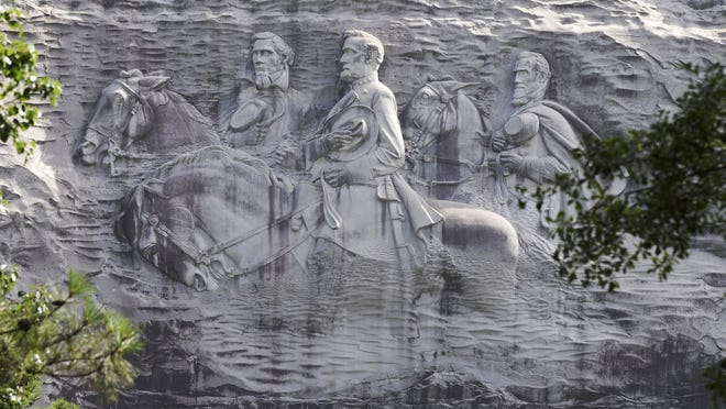 This 2015 file photo shows a carving depicting Confederate Civil War figures Stonewall Jackson, Robert E. Lee and Jefferson Davis, in Stone Mountain, Ga. The sculpture is America's largest Confederate memorial.