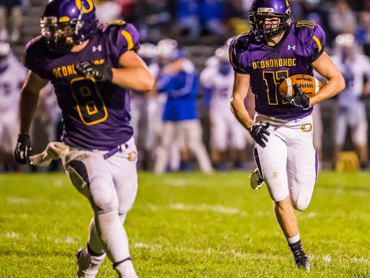 Oconomowoc senior Nate Nord (11) follows teammate Nick Gomez (8) into the end zone for a touchdown in the fourth quarter against Wisconsin Lutheran on Friday, Sept. 27, 2013.