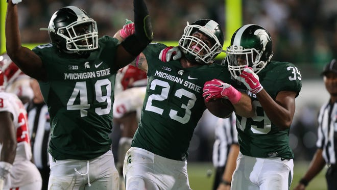 (From left) Michigan State's Spartans Shane Jones, Chris Frey and Jermaine Edmondson celebrate after recovering a fumble during the second half Saturday in East Lansing.