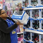 Toy department manager Gayla Harris stocks shelves for Black Friday sales at a Wal-Mart store in Oklahoma City on Nov. 26, 2013.
