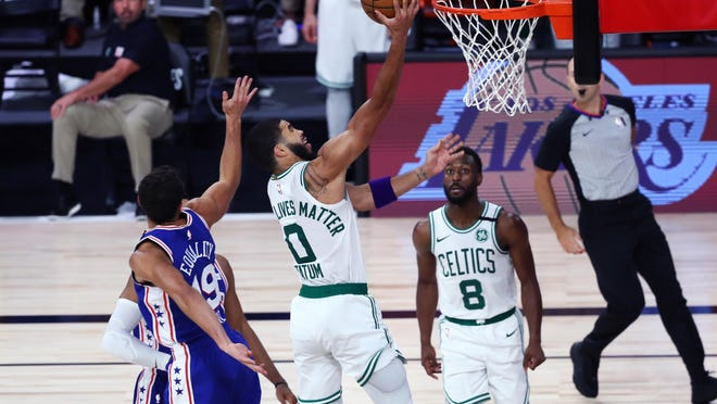 Celtics forward Jayson Tatum (0) shoots past 76ers guard Raul Neto (19) during the fourth quarter of Game 4 of their first-round playoff series on Sunday.