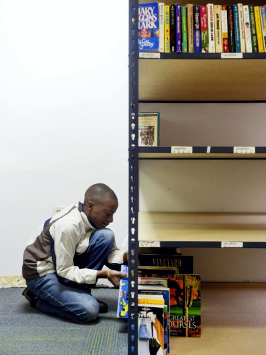 Qushaun Lindsey, 12, a sixth-grade student at Ferguson K-8 School, shelves books at Po's Bookstore on South George Street in downtown York.