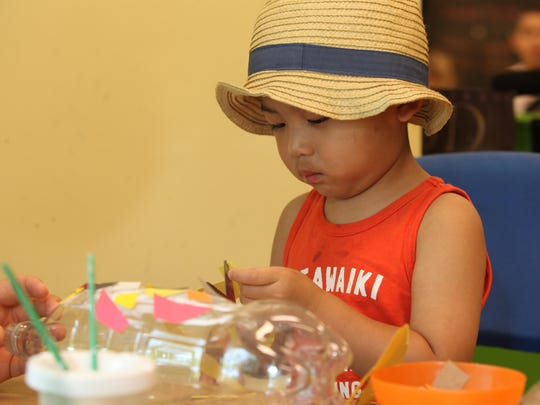 Two-year-old Brendan Song of Brandywine Hundred cuts a piece of paper to decorate his rocket Sunday at the Delaware Children's Museum in Wilmington.