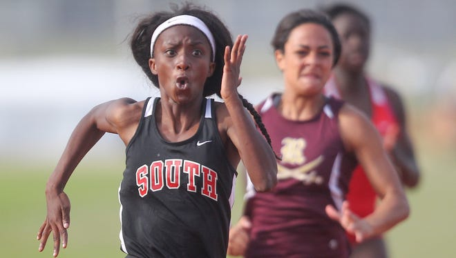 South Fort Myers runner Mirlege Castor, left, wins the girls 100 meter dash Wednesday at the District 3A-11 track and field meet in Punta Gorda with a time of 25.41.