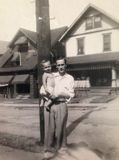 In this family photo, Eugene Flynt holds his young son, Jimmy, in the Goodyear Heights neighborhood in Akron, Ohio.