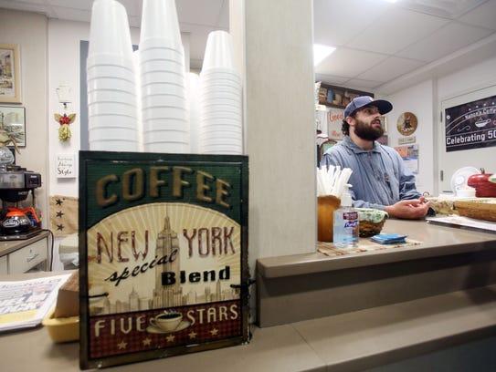 Sean Cohen waits on a customer at Nance's Coffee inside