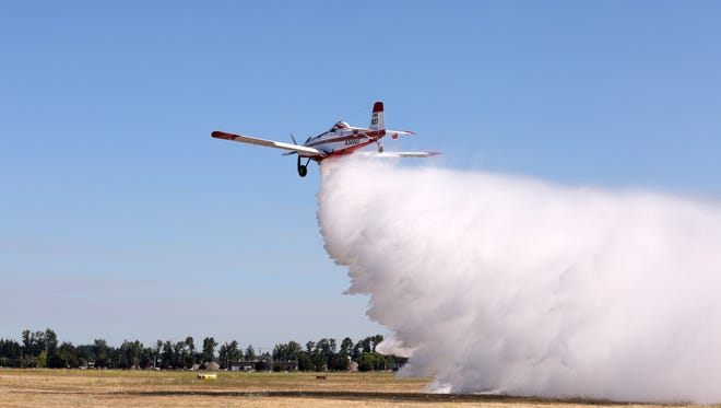 A single-engine air tanker, flown by contract pilot Doug Hodges, drops water along the runway on Friday, July 29, 2016, near the Oregon Department of Foresty hanger at the Salem Municipal Airport as part of a firefighter training exercise.