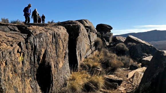 Participants in Tuesday's BackTrek charity hike examine petroglyphs at the Land Hill Heritage Site near Ivins City.