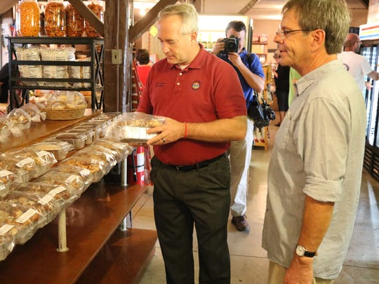 Ohio Senate Pres. Keith Faber checks out the locally baked breads at Bergman Orchards, joined by owner Dan Bergman, right.