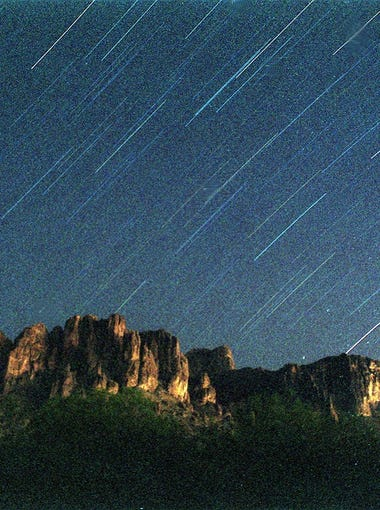 Star trails over Superstitution Mountains  in this photo taken Aug. 12, 1999 during a meteor shower with  a 20-minute time exposure.  Two of the streaks in the center are from meteors; they look the same as a star trail.