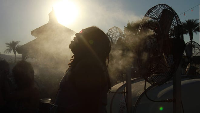 Robel Douglas of Van Nuys, Calif. takes a moment to cool off by a water misting fan as temperatures climbed into triple digits on Sunday afternoon, April 22, 2012 during the last day of the Coachella Valley Music and Arts Festival's second weekend at Empire Polo Club in Indio, Calif. Crystal Chatham, The Desert Sun