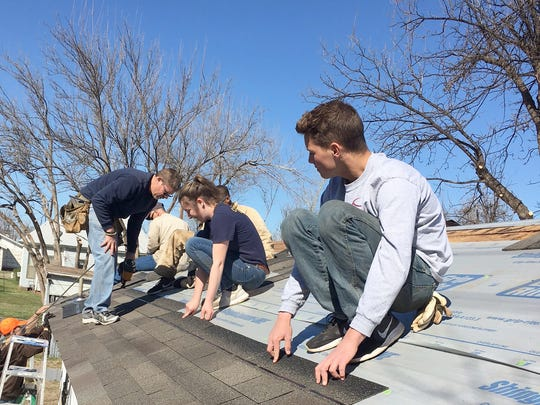 Vernon contractor David Logsdon, far left, gives advice to young roofers working on the first house to receive new shingles as part of Ethan Curtis' service project. Ethan, right,  keeps the shingles straight.