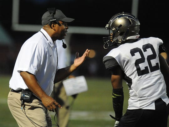 Timber Creek head football coach Rob Hinson talks to running back Harold Coleman between plays against Delsea in September.