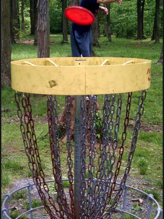Ben Fisher lands a disc golf putt at the Boulder Woods course at Pinchot State Park.