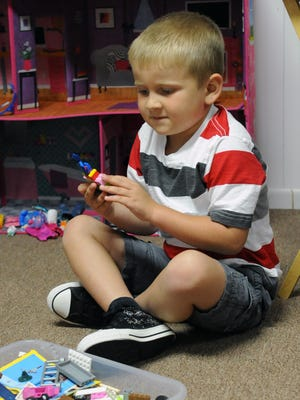 Owen Mottie plays with Legos at his house Thursday in Chillicothe. Mottie will be in the pits at the Nationwide Children's Hospital 200 next weekend as a Patient Champion.