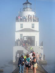 Fog envelops the lighthouse as people line up along the breakwater wall to get a close look at the new renovations during Subfest Saturday, July 14, 2018, in Manitowoc, Wis. The lighthouse was open to the public during a ribbon cutting ceremony to celebrate the new renovations. Josh Clark/USA TODAY NETWORK-Wisconsin