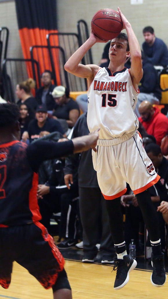 Mamaroneck's Jared Bader (15)  puts up a shot in front of Spring Valley's Christopher White (2) during Section 1 boys basketball playoff action at Mamaroneck High School Feb. 23, 2018. Mamaroneck won the game 49-42.