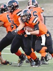 Northville quarterback Jon Michalak (with ball) follows a convey of blockers.
