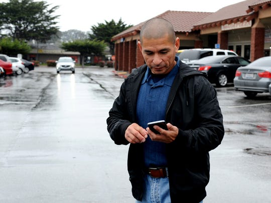 Johnny Plancencia checks his phone as he heads to his car in a Marina parking lot.