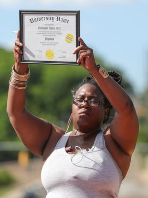 At a protest in Akron on Tuesday afternoon, Danique McGee, a cousin of Na'Kia Crawford, holds a blank college diploma frame to symbolize the recent high school graduate's lost future. Crawford was fatally shot Sunday afternoon while driving with her grandmother.
