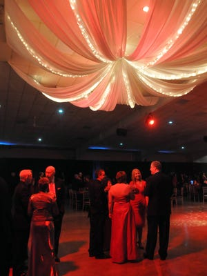 Guests visit under a soft canopy of light and fabric in the Kuhlman Center on the Wayne County Fairgrounds during the Red Dress Ball.