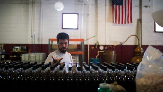 Chief distiller James Yoakum counts bottles of brandy at Cooper River Distillers in Camden. The distillery is now part of the Philadelphia Area Distillery Trail.