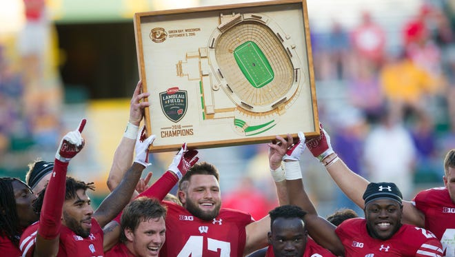 Wisconsin players holds up the Lambeau Field College Classic trophy following a 16-14 victory over LSU on Sept. 3.