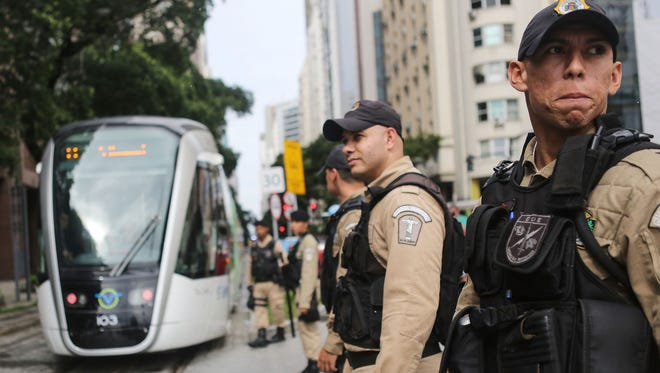 Police watch as a new VLT (Light Rail Vehicle) passes on the day the system was inaugurated ahead of the upcoming Rio Olympic Games on June 5, 2016 in Rio de Janeiro.