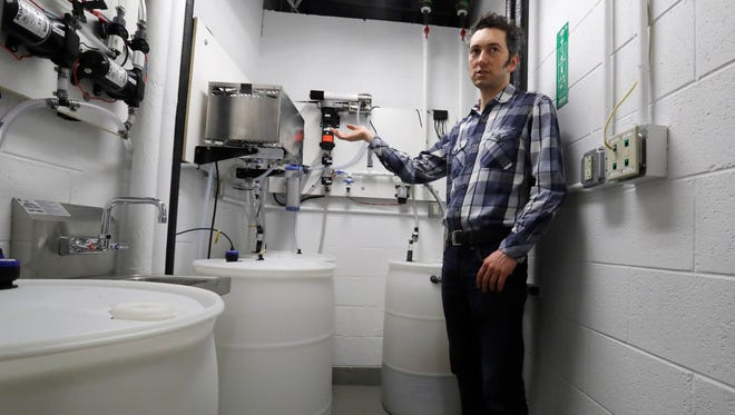 Abe Noe-Hays, director of research at the Vermont-based Rich Earth Institute describes the filtration system he helped develop to turn urine into fertilizer at the University of Michigan engineering building.