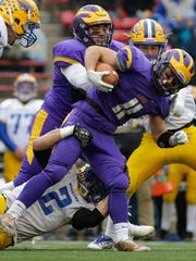 New Berlin Eisenhower running back Jake Belongia is tackled by Rice Lake's Averie Habas (2) during their WIAA Division 3 state football championship game at Camp Randall Stadium.