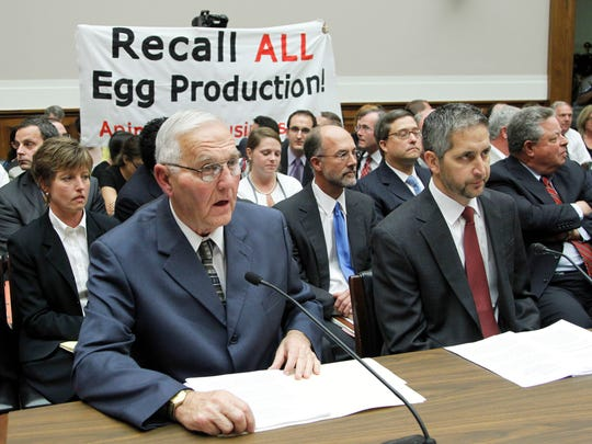 "Protestors unfurl a banner on Capitol Hill in Washington in 2010 as Wright County Egg owner Austin ""Jack"" DeCoster, left, and Chief Operating Officer Peter DeCoster, right, testify before a House oversight and investigations subcommittee hearing on the outbreak of salmonella contamination in eggs."