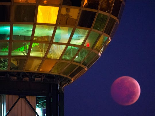 "A total lunar eclipse spawns a ""blood moon"" as it dips beneath the Sunsphere in Knoxville on Oct. 8, 2014. During a total lunar eclipse, the moon is lit only by sunlight, which has scattered through the Earth's atmosphere, stripping out all colors except red."
