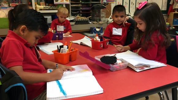 Myrtle Cooper Elementary School students color a picture in their prekindergarten class.