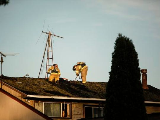 Firefighters work from the roof of the Country House Catering and Banquet Hall on Okemos Road  Wednesday evening.  Firefighters from several area departments responded to the fire.  No one was injured.  The cause of the fire is under investigation.