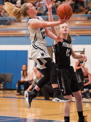 Novi's Ellie Mackay, left, jumps the ball to the basket