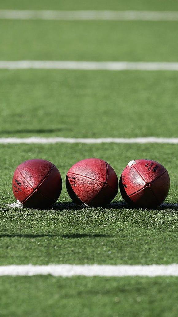 Three footballs lay on football field.