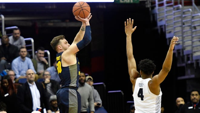 Marquette's Andrew Rowsey puts up a three-pointer over  Georgetown guard Jagan Mosely in overtime