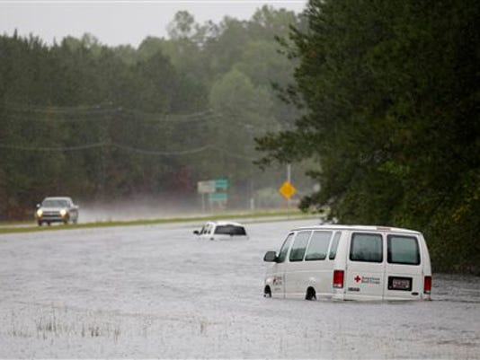 An American Red Cross van is stranded in floodwaters on U.S. Hwy. 17 North near Georgetown, S.C., Sunday, Oct. 4, 2015. Several sections of Highway 17 are shut down between Charleston and Georgetown. (AP Photo/Mic Smith)