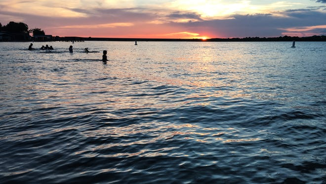 Kids swim at sunset at Lake Nasworthy.