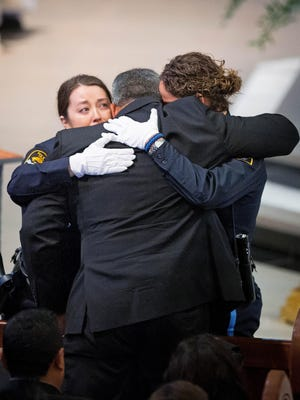 Two Omaha police officers embrace Hector Orozco, the husband of Kerrie Orozco, near the end of her funeral service Tuesday, May 26, 2015 at St. John's Catholic Church at Creighton University in Omaha,. Orozco, 29, was shot and killed May 20 in Omaha.