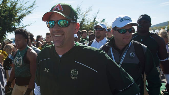 CSU head football coach Mike Bobo walks in a parade during the tailgate outside Hughes Stadium before the Rams take on Air Force Saturday, October 17, 2015.