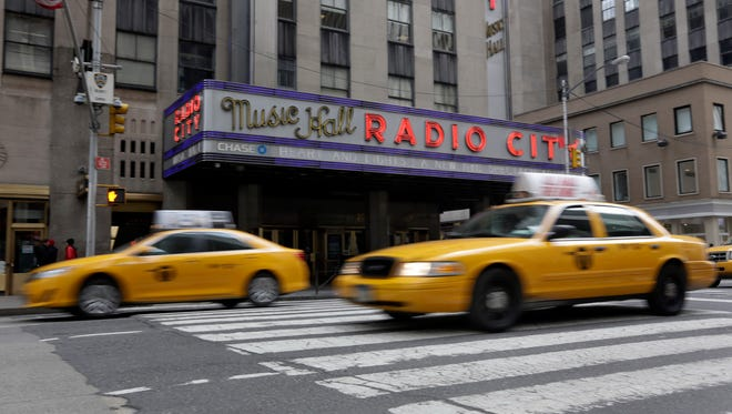 New York City taxis pass  New York's Radio City Music Hall, Thursday, Feb. 27, 2014. Under ambitious proposals that seek to get New York City cabs to slow down by taking the financial incentive out of speeding, black boxes inside cabs would shut the toll meter off whenever a cab goes above the posted limit - 25 mph in much of Manhattan - and drivers would be alerted they are going too fast.