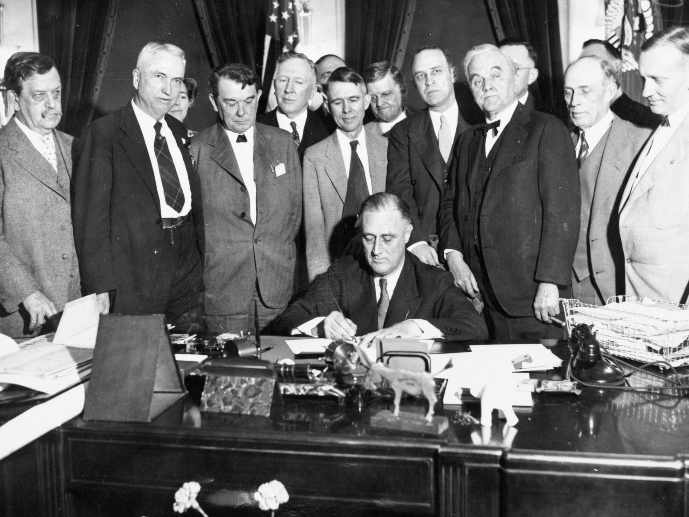 President Franklin D. Roosevelt signs the TVA Act on May 18, 1933. The president is surrounded by members of Congress from the TVA region, and at his left shoulder is Sen. George Norris of Nebraska, after whom Norris Dam is named.