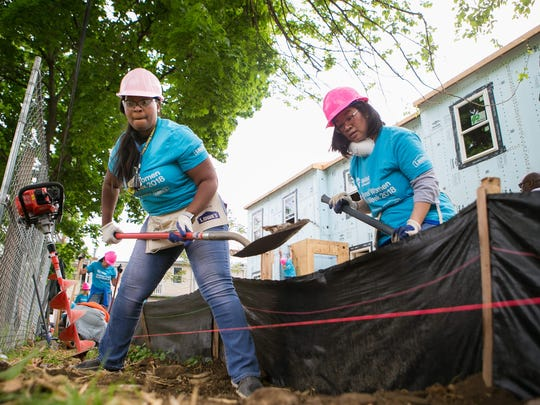 Kimwanda Robeson (left) and Sally Cheung with JPMorgan Chase work on the backyard fencing as they join other local women who contribute their time working alongside future homeowner Sheniquia Brown to assist in the construction of her Habitat for Humanity home as part of the National Women Build Week.