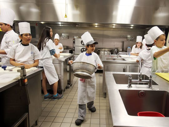 Dev Thawani, 10, of Canton, center,  grabs a colander for his group during Day 1 of Henry Ford Community College's culinary kids camp in Dearborn on Monday, June 15, 2015.