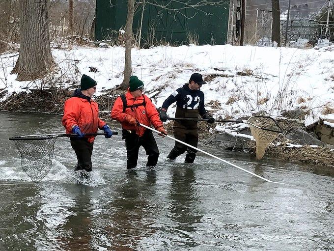 DEC staffers wade along Catharine Creek on Monday looking