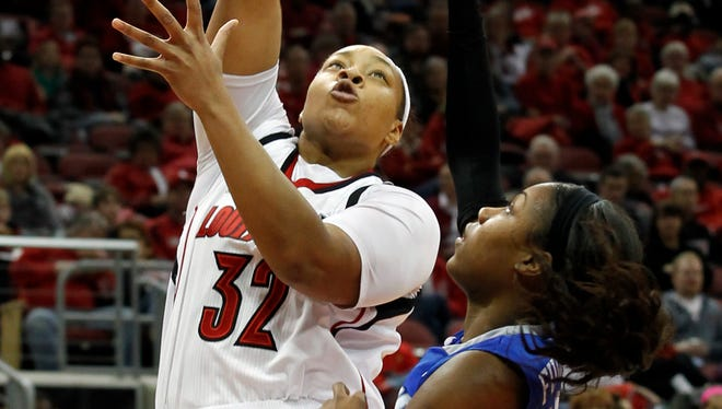 University of Louisville's Emmonnie Henderson (32) fights to get her shot off under pressure from University of Memphis' Asianna Fuqua-Bey (21) during the second half of play at the KFC Yum! Center in Louisville, Kentucky.       January 26, 2014
