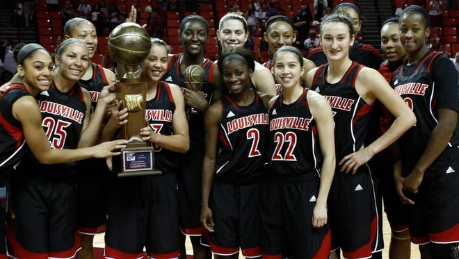The Louisville Cardinals hold the Preseason WNIT Tournament trophy after defeating the Oklahoma Sooners at Lloyd Noble Center.
