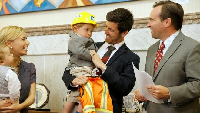 Mayor John Cranley smiles at 2-year-old Quincy Kroner and his father, Oliver, and his mother Libby, after giving Quicy a custom-made sanitation worker uniform.