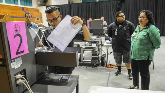 In this file photo, Albert Sanga removes a mock election ballot from a tabulator  during a test run at the University of Guam Calvo Field House. Elected officials and our government should clear obstacles to the ballot box.